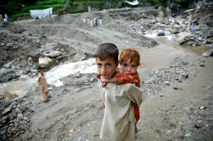 Ifthikar, 5 years old, carries his sister her Sfia, 2 years old in hope they can find some help.