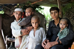 Sher Ali, 14 years old, sitting with his brothers in a temporary shelter he made after his house washed away due to flood.