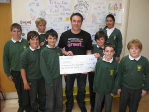Simon and children from St. Joseph's with a £434.89 Cheque for CAFOD.