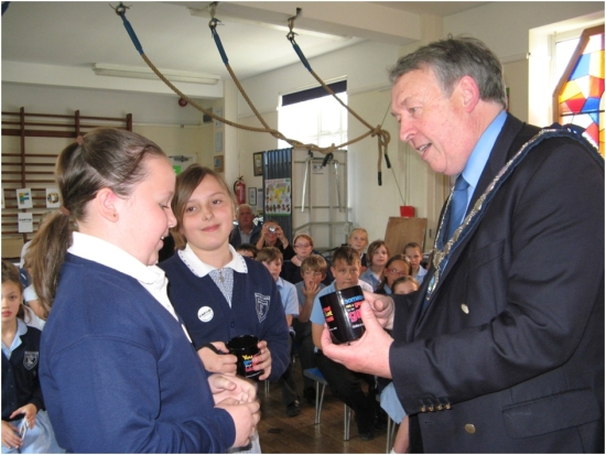 Councillor Bill Brite presents a delighted pupil with a CAFOD mug to award a great speech on social justice issues regarding the global food system.