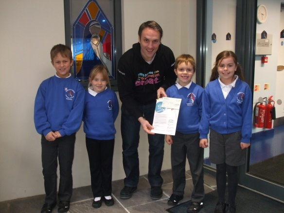 Children from St Mary's presenting a cheque for £158 to Simon Giarchi from CAFOD Plymouth
