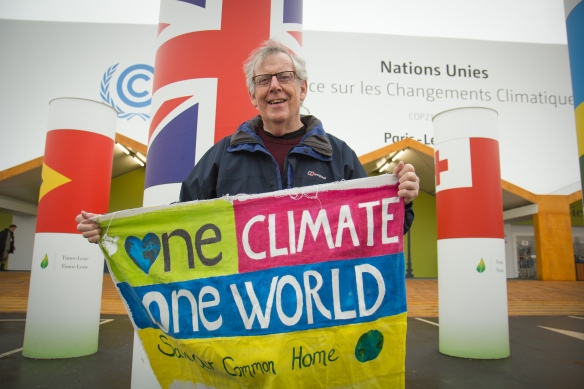 Man holding a sign saying 'one climate, one world'
